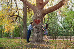 Couple peeking around opposite sides of tree. Concept of love story and dating Stock Image