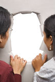 Couple peeking through hole in wall Stock Images