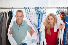 Couple Peeking Through Shirts Hanging From Rack Stock Image
