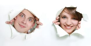 Couple peeping through hole in paper Stock Photos