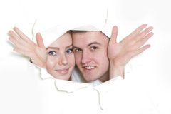 Couple peeping through hole in paper Royalty Free Stock Images
