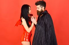 Couple on pensive faces play role game. Devil love concept. Man and woman dressed like vampire, demon, red background royalty free stock photos