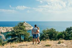 Couple people embracing on journey on holiday in the mountains by the sea on summer day. Couple of young people embracing on journey on holiday in the mountains Stock Images
