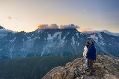 Couple of people looking at the sunrise over Mont Blanc mountain peak 4810 m. Valle d`Aosta, italian summer adventures and trav Stock Photography