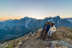 Couple of people looking at the sunrise over Mont Blanc mountain peak 4810 m. Valle d`Aosta, italian summer adventures and trav Stock Images