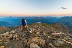 Couple of people looking at the sunrise over Mont Blanc mountain peak 4810 m. Valle d`Aosta, italian summer adventures and trav Royalty Free Stock Images
