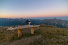 Couple of people looking at the sunrise over Mont Blanc mountain peak 4810 m. Valle d`Aosta, italian summer adventures and trav Royalty Free Stock Photography