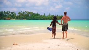Couple people in love having fun on the beach. A loving couple enjoying the breathtaking views of the tropical sandy beach with green coconut palm trees and stock video footage