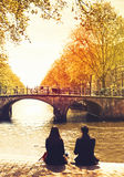 Couple people relaxing in Amsterdam city. Couple friends or lovers relaxing on embankment of canal and looks at the river and bridges of Amsterdam. Photo toning stock image