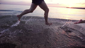 Couple people running in shallow water at sunset in slow motion. Spray from the fleeing feet Man and girl on waterfront sea in slow-mo. Crazy jogging on the stock video footage