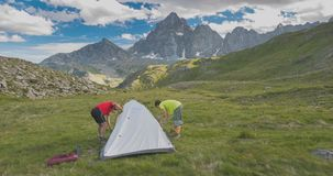 Couple of people setting up a camping tent on the mountains, time lapse. Adventures on the Alps, majestic peak in the backgrou. Nd M. Viso, 3841 m, Torino stock video