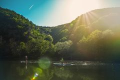 A couple of people slowly floating on the river on the sup-board, against the mountains and blue sky.  royalty free stock images