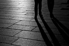 Couple of people and their shadows. Pair of passing shadows walking in a sunny square in the city Stock Photos