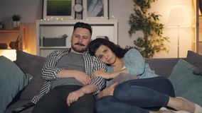 Couple of people watching sad movie on TV sitting on sofa at home together stock footage