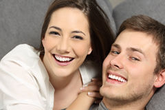 Couple with perfect teeth and white smile. Happy couple with perfect teeth and white smile lying on a couch and looking at you Royalty Free Stock Photo