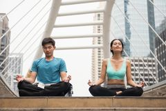 Couple perform lotus hand pose  yoga in city. Asian young male and female couple perform yoga in lotus hand pose meditation in modern city. Healthy and sport Stock Photography