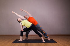 Couple perform series of Extended Side Angle yoga partner pose Royalty Free Stock Photography