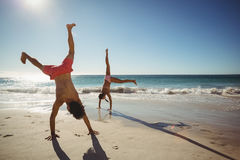 Couple performing somersault on beach. In summer Royalty Free Stock Images