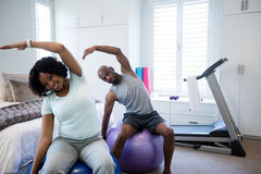 Couple performing stretching exercise on fitness ball in bedroom Royalty Free Stock Photos