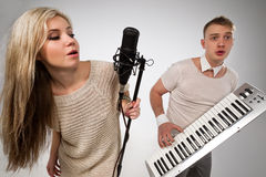 Singers. Couple performs duet singing microphone and plaing on synthesizer Stock Image