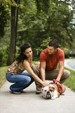 Couple petting dog. Royalty Free Stock Images