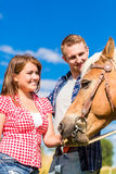 Couple petting horse Stock Images