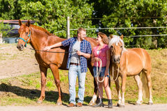 Couple petting horse on stable Royalty Free Stock Photos