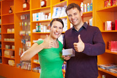 Couple in pharmacy holding thumbs. Happy couple in a pharmacy holding their thumbs up Stock Photography