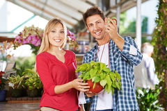 Couple with philodendron in a nursery shop. Happy couple with a green philodendron in a nursery shop stock photos