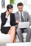 Couple with phone and laptop Stock Image