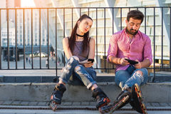 Couple with phones is sitting. royalty free stock photography