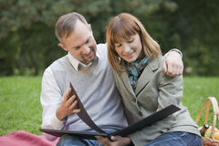 Couple with photo album outdoors Stock Image