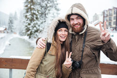 Couple with photo camera showing peace gesture on winter resort Royalty Free Stock Photography