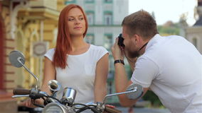 Couple is photographed on a scooter. Attractive couple is photographed on a scooter on a sunny day in the city stock footage