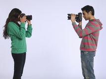 Couple Photographing Each Other In Studio Stock Image