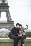 Couple Photographing In Front Of Eiffel Tower. Young couple taking self portrait in front of Eiffel tower Royalty Free Stock Images