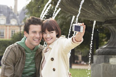 Couple Photographing In Front Of Fountain Stock Image