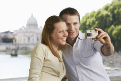 Couple Photographing Selves With Digital Camera Stock Photography