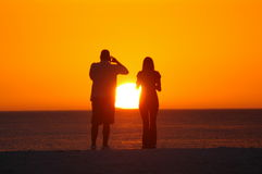 Couple photographing sunset Royalty Free Stock Photos