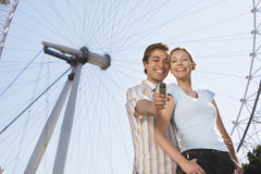 Couple Photographing Themselves Against London Eye Royalty Free Stock Photos