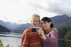 Couple Photographing Themselves Against The Mountains. Middle aged couple photographing themselves with mountains in the background Royalty Free Stock Photos