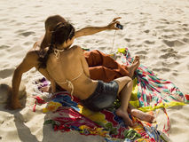 Couple photographing themselves at the beach. Stock Photography