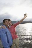 Couple Photographing Themselves On Beach Royalty Free Stock Images