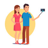 Couple photographing themselves on selfie stick Royalty Free Stock Photos