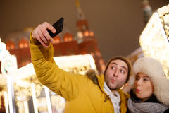Couple photographing themselves on street. Beautiful couple photographing themselves on street in winter Stock Image
