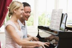 couple piano playing smiling Στοκ φωτογραφία με δικαίωμα ελεύθερης χρήσης