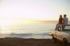Couple On Pick-Up Truck Parked In Front Of Ocean. Rear view of young couple on pick-up truck parked in front of ocean enjoying sunset Royalty Free Stock Image