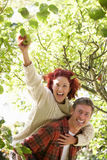 Couple picking apples off tree Stock Images