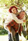 Couple picking apples off tree Stock Photos