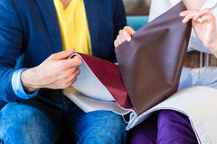 Couple picking couch seat cover in furniture store Royalty Free Stock Images